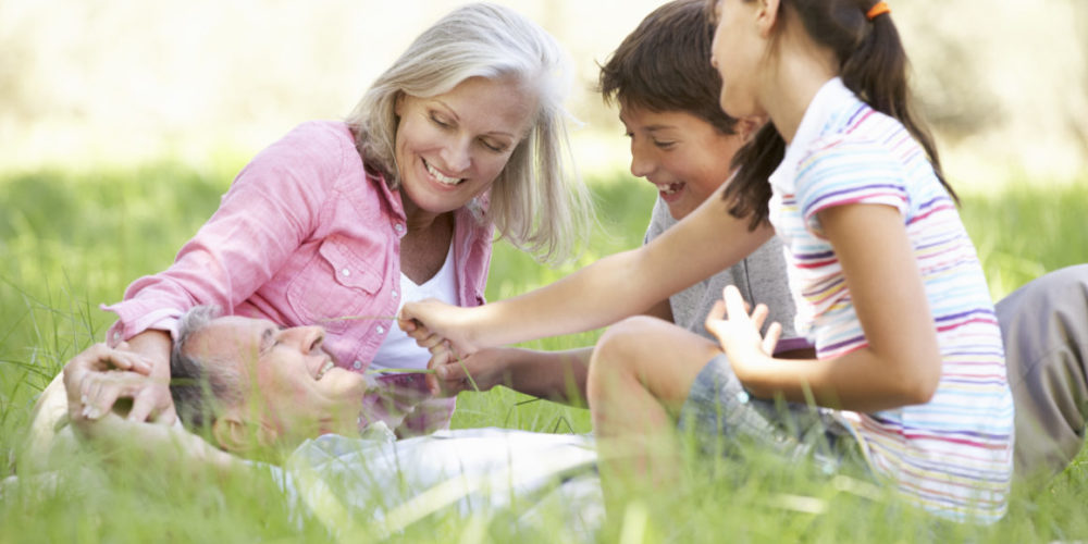 Grandparents With Grandchildren Relaxing In Summer Field